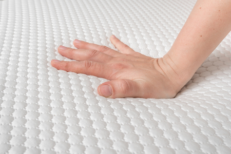 Woman is choosing new mattress for good sleeping. Hand of woman is testing mattress quality.