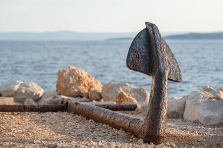 Old rusty anchor on the beach with stones on sunset