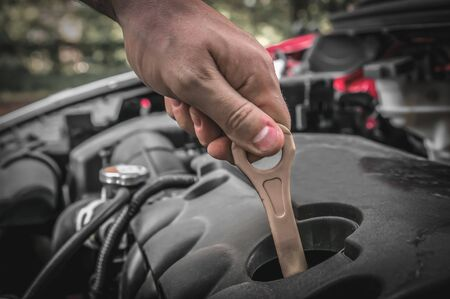 Mechanic checking the oil level in a car engine - car service concept