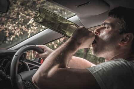 Drunk driver with bottle of beer is driving a car - alcohol in car concept