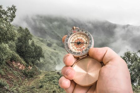 Traveler man with compass seeking a right way through the fog in mountains - navigation concept