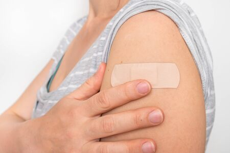 Woman with adhesive bandage on her shoulder - injury concept