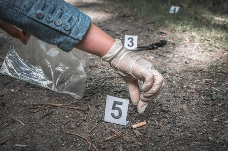 Investigator collects evidence (cigarette butt) - crime scene investigation Stock Photo