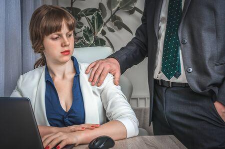 Mann berührt die Schulter einer Frau - Belästigung im Geschäftsbüro