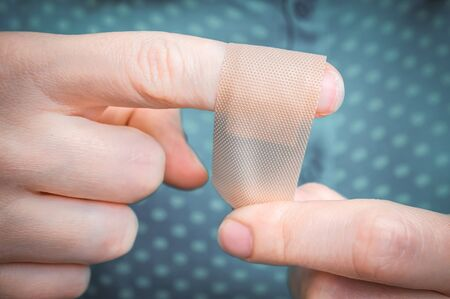 Young woman puts a plaster on her injured finger Imagens