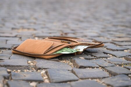 Lost leather wallet with money on the ground on street 스톡 콘텐츠