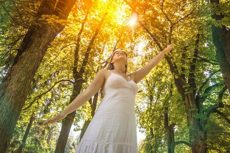 Young woman is enjoying sunshine on a sunny day in forest