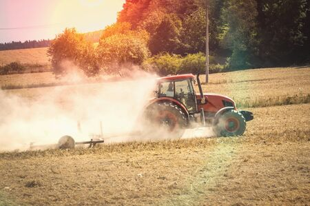 Red tractor plows a field - agriculture and agronomy concept