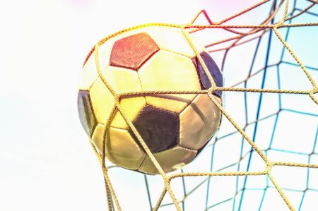 Soccer ball in the goal net with blue sky background and sunset