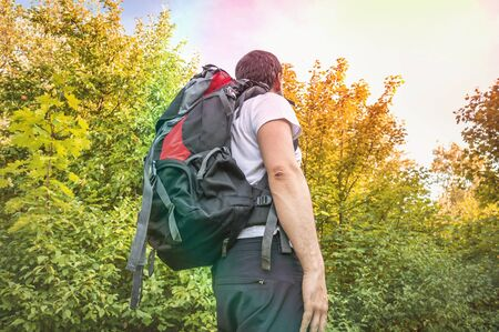 Traveler man with red backpack is walking in autumn forest - hiking concept