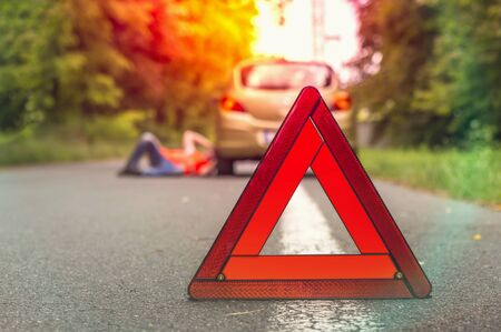Driver lying under the broken car and traffic warning triangle