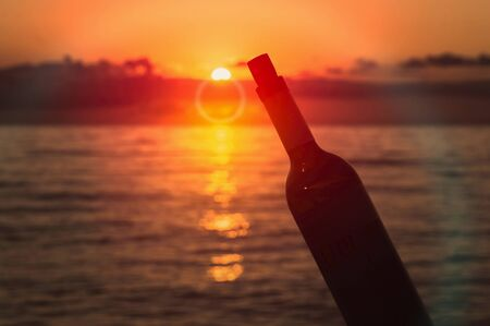 Beautiful sunset on sea and silhouette of a bottle of wine 스톡 콘텐츠