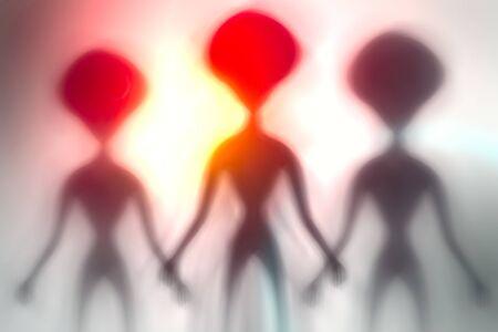 Siluetas de extraterrestres espeluznantes y luz brillante detrás de ellos. Concepto OVNI. Foto de archivo