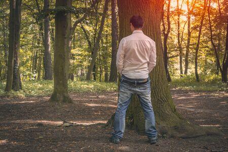 Hombre de pie orinando cerca de un gran árbol en el bosque de otoño en la naturaleza - concepto de incontinencia Foto de archivo