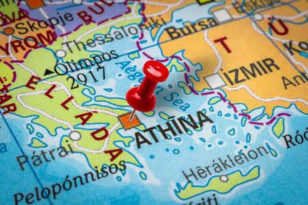 PRAGUE, CZECH REPUBLIC - OCTOBER 28, 2019: Red thumbtack in a map. Pushpin pointing at Athens city in Greece.