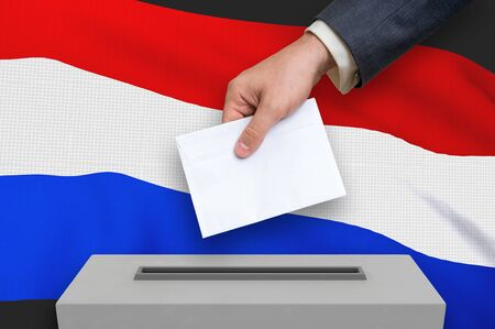 Election in Netherlands - voting at the ballot box. The hand of man is putting his vote in the ballot box. 3D rendered illustration. Фото со стока