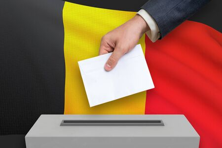 Election in Belgium - voting at the ballot box. The hand of man is putting his vote in the ballot box. 3D rendered illustration. Imagens