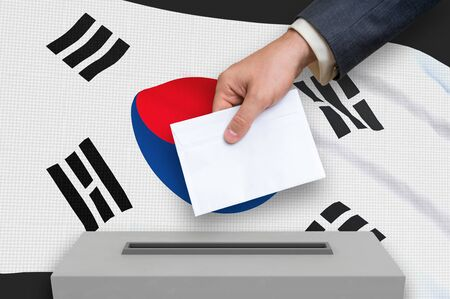 Election in South Korea - voting at the ballot box. The hand of man is putting his vote in the ballot box. 3D rendered illustration. Stok Fotoğraf - 133458345