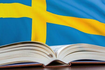 Education in Sweden. Opened book and national flag on background. 3D rendered illustration. Stock fotó