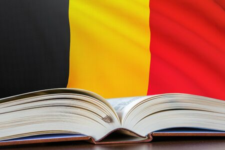 Education in Belgium. Opened book and national flag on background. 3D rendered illustration. Imagens