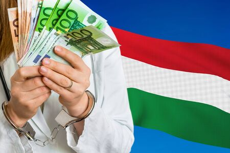 Medical corruption and bribery in Hungary. Doctor with handcuffs and with money on national flag background. Archivio Fotografico