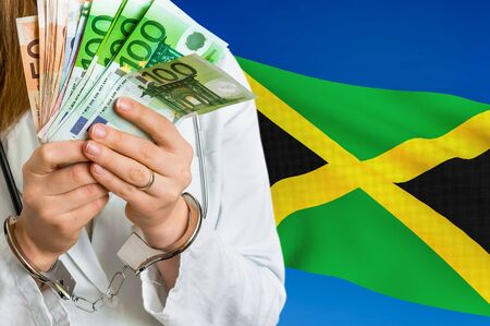 Medical corruption and bribery in Jamaica. Doctor with handcuffs and with money on national flag background. Stock Photo
