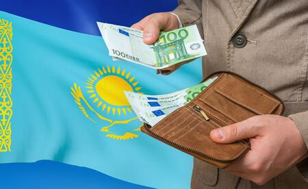 Investing money to Kazakhstan. Rich man with a lot of money in his hands and national flag on background. Stok Fotoğraf