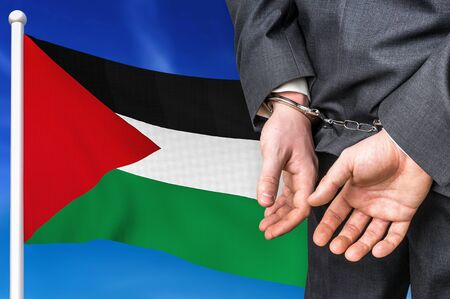 Prisons and corruption in Palestine. Businessman with handcuffs on national flag background.