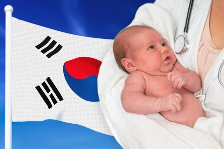 Birth rate in South Korea. Newborn baby in hands of doctor on national flag background. Archivio Fotografico - 137885757