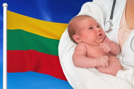 Birth rate in Lithuania. Newborn baby in hands of doctor on national flag background. Archivio Fotografico - 137885766