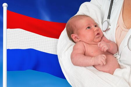 Birth rate in Netherlands. Newborn baby in hands of doctor on national flag background. Archivio Fotografico - 137885772
