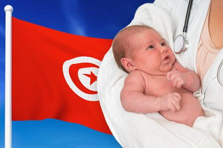 Birth rate in Tunisia. Newborn baby in hands of doctor on national flag background. Archivio Fotografico - 137885811