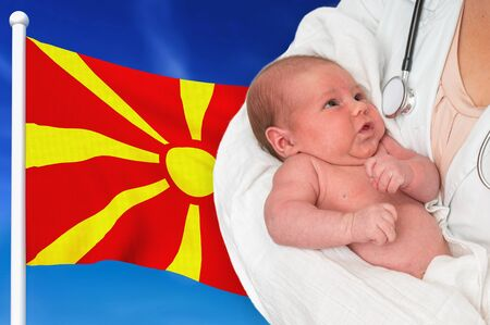 Birth rate in Macedonia. Newborn baby in hands of doctor on national flag background. Archivio Fotografico - 137885822