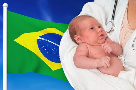 Birth rate in Brazil. Newborn baby in hands of doctor on national flag background. Archivio Fotografico - 137885831