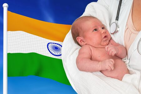 Birth rate in India. Newborn baby in hands of doctor on national flag background. Archivio Fotografico - 137885835