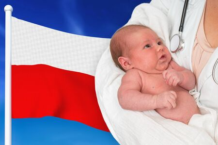 Birth rate in Poland. Newborn baby in hands of doctor on national flag background. Archivio Fotografico - 137885907