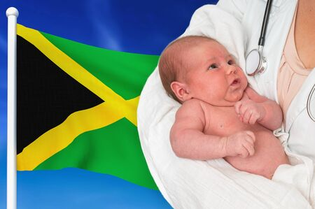 Birth rate in Jamaica. Newborn baby in hands of doctor on national flag background. Archivio Fotografico - 137885910