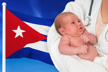 Birth rate in Cuba. Newborn baby in hands of doctor on national flag background. Stock fotó