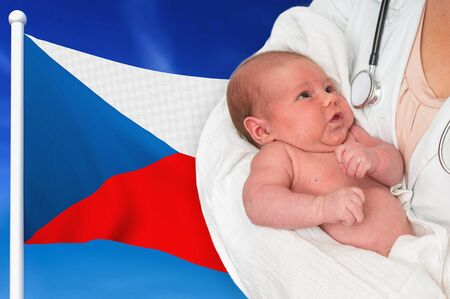 Birth rate in Czech Republic. Newborn baby in hands of doctor on national flag background.
