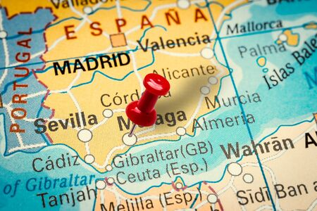 PRAGUE, CZECH REPUBLIC - JANUARY 12, 2019: Red thumbtack in a map. Pushpin pointing at Malaga city in Spain.