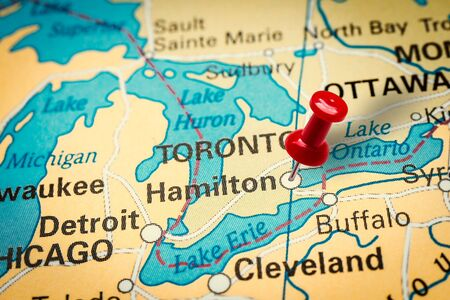 PRAGUE, CZECH REPUBLIC - JANUARY 12, 2019: Red thumbtack in a map. Pushpin pointing at Hamilton city in Ontario, Canada.