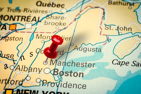 PRAGUE, CZECH REPUBLIC - JANUARY 12, 2019: Red thumbtack in a map. Pushpin pointing at Manchester city in New Hampshire, America.
