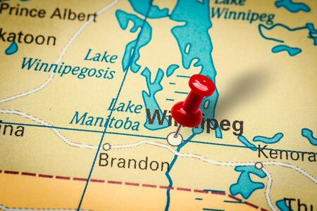PRAGUE, CZECH REPUBLIC - JANUARY 12, 2019: Red thumbtack in a map. Pushpin pointing at Winnipeg city in Canada.
