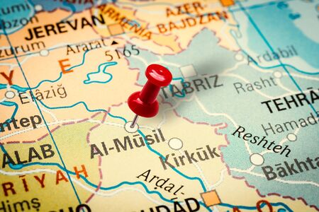 PRAGUE, CZECH REPUBLIC - JANUARY 12, 2019: Red thumbtack in a map. Pushpin pointing at Mosul city in Iraq. Stock fotó