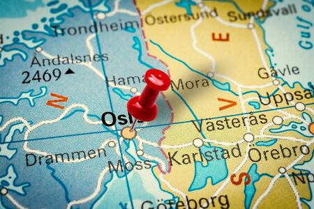 PRAGUE, CZECH REPUBLIC - JANUARY 12, 2019: Red thumbtack in a map. Pushpin pointing at Oslo city in Norway.