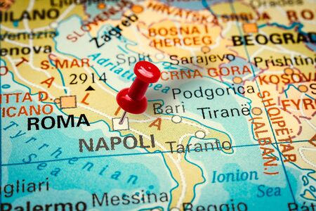 PRAGUE, CZECH REPUBLIC - JANUARY 12, 2019: Red thumbtack in a map. Pushpin pointing at Naples city in Italy.