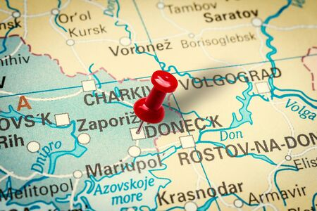 PRAGUE, CZECH REPUBLIC - JANUARY 12, 2019: Red thumbtack in a map. Pushpin pointing at Donetsk city in Ukraine. Stock fotó
