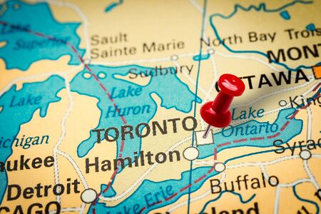 PRAGUE, CZECH REPUBLIC - JANUARY 12, 2019: Red thumbtack in a map. Pushpin pointing at Toronto city in Canada.