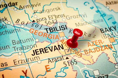 PRAGUE, CZECH REPUBLIC - JANUARY 12, 2019: Red thumbtack in a map. Pushpin pointing at Yerevan city in Armenia.