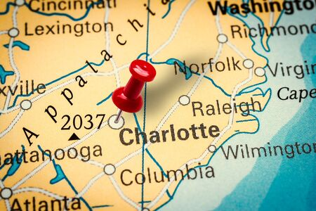 PRAGUE, CZECH REPUBLIC - JANUARY 12, 2019: Red thumbtack in a map. Pushpin pointing at Charlotte city in North Carolina, America. Sajtókép
